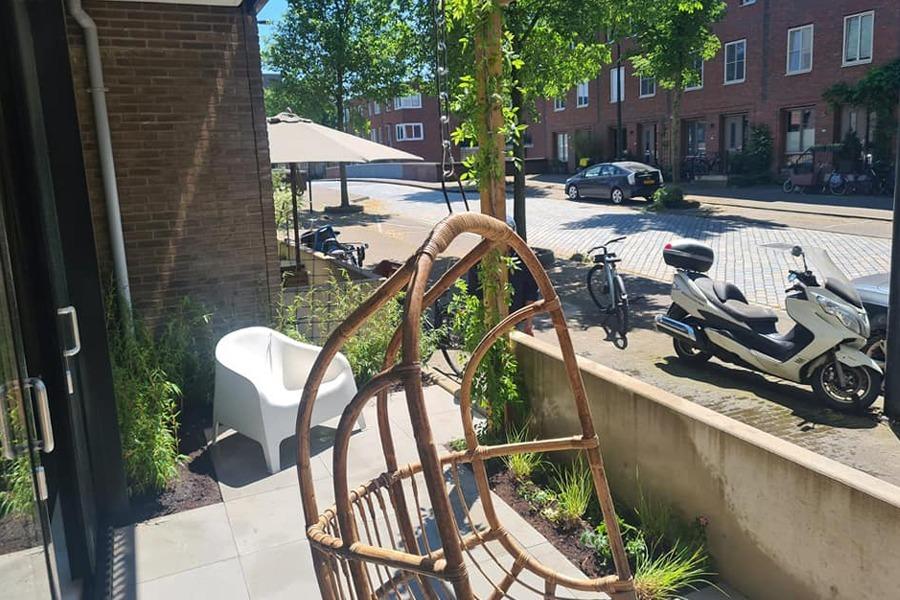 Balkon met straatbeeld. Bamboe hangstoel, tegels en beplanting.