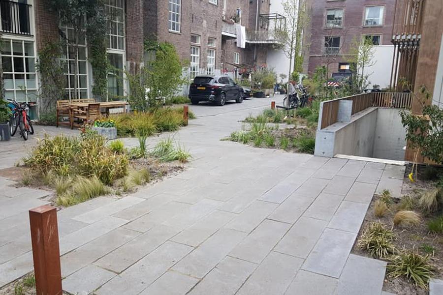 Aangelegde binnenplaats voor een vve in de stad. Met beplanting, tegels en vlakken.