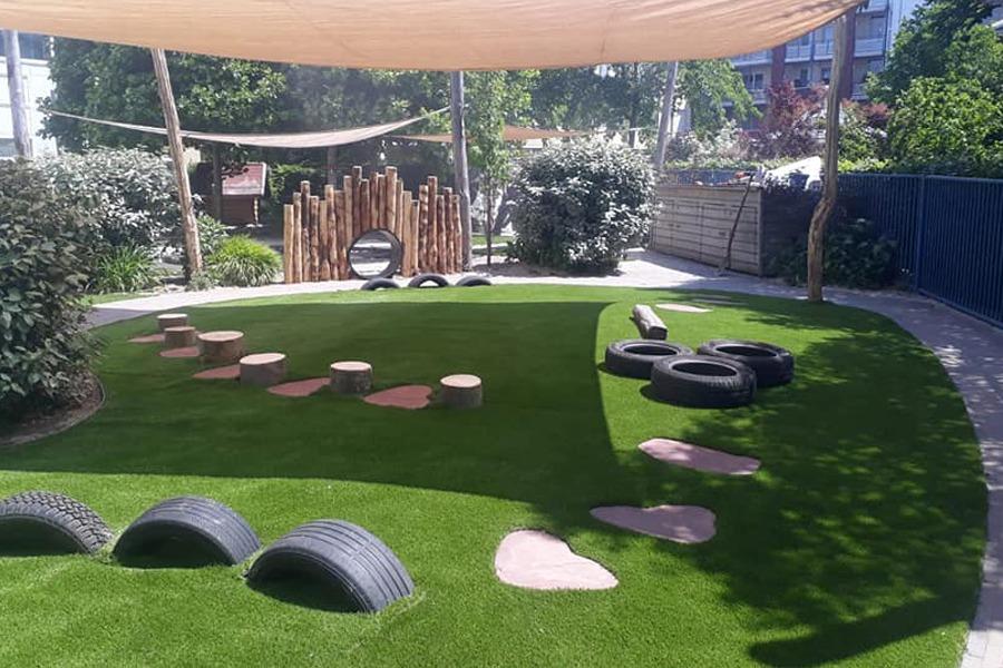 Voorbeeld van een aangelegde speeltuin met kunstgras, loopstenen, speeltoestellen en beplanting