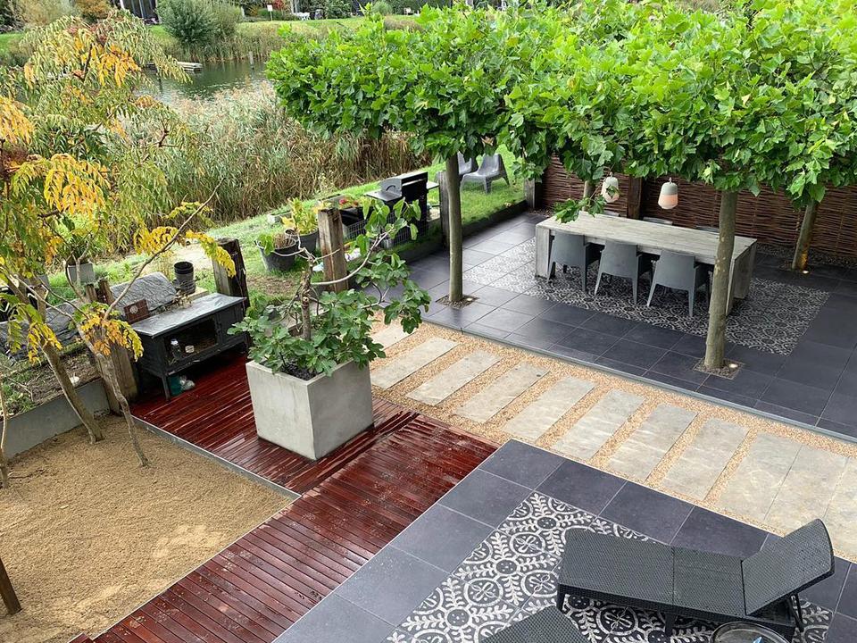 Voorbeeld van een aangelegde tuin. Met bestrating, bomen, terras, verlichting, vlonders, eethoe en zithoek